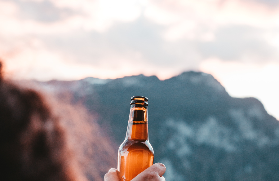 hand holding a beer bottle celebrating the start of this adventures in technology blog with a mountain backdrop